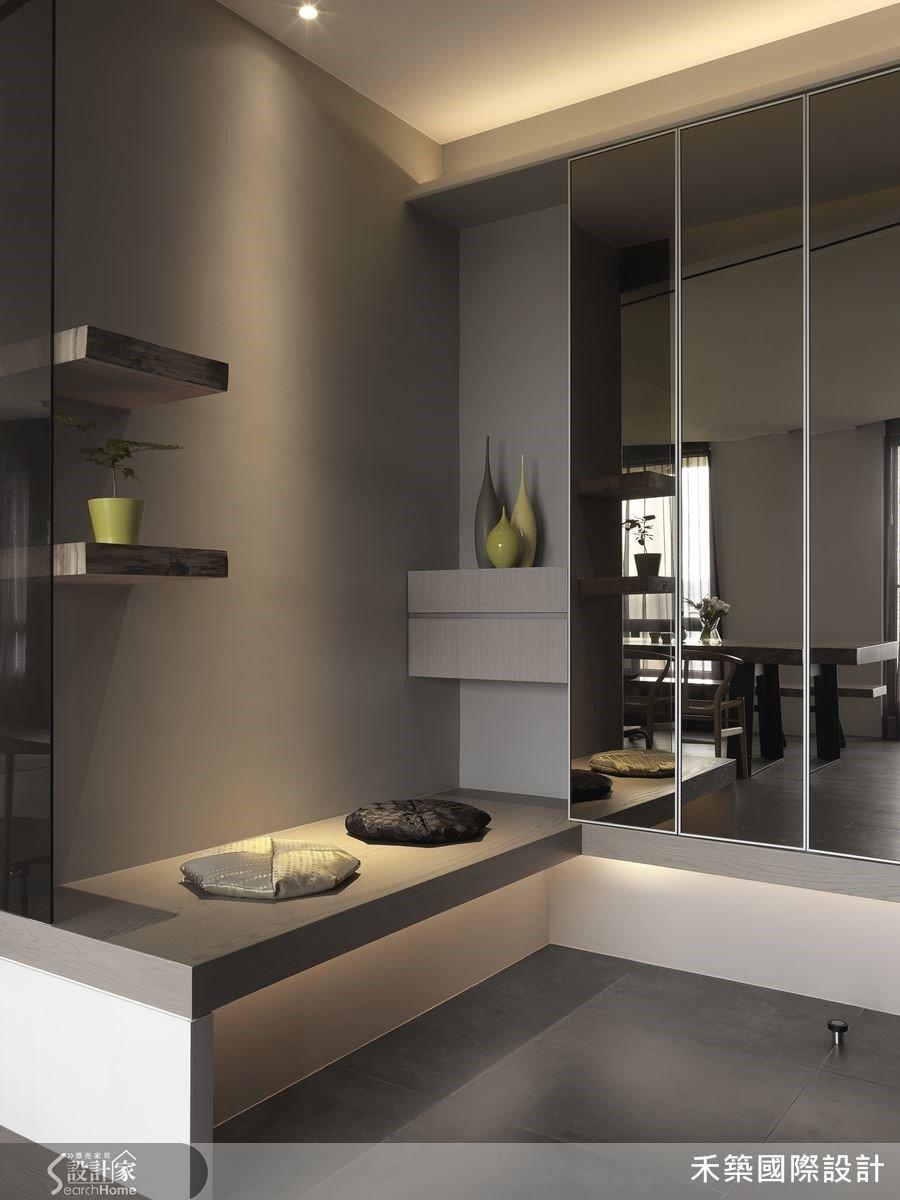 玄關區不落地的收納櫃與座椅結合,搭配間接照明,讓量體變輕盈,減輕壓迫感。