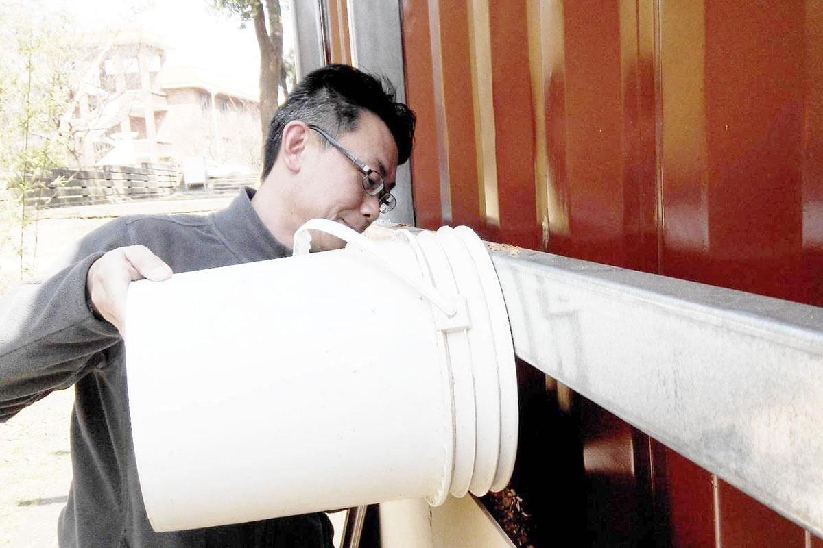 江益璋教授示範將無機木屑棉填充至貨櫃的金屬外殼與鑽泥板層之間。